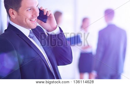 Portrait of young businessman in office with colleagues in the background and using mobile