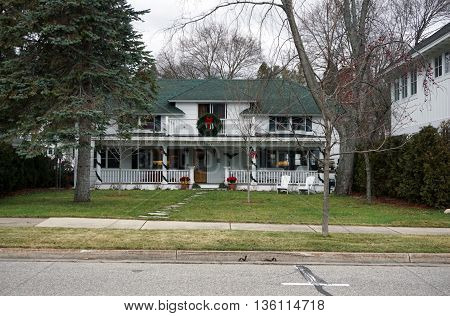 HARBOR SPRINGS, MICHIGAN / UNITED STATES - DECEMBER 24, 2015: A Harbor Springs home is festively decorated for Christmas with garlands, ribbons and wreaths.