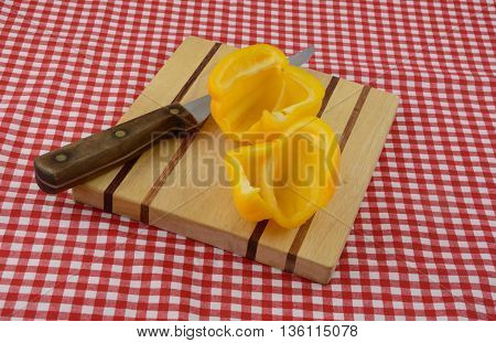 Cleaned Yellow bell pepper halves on cutting board with knife