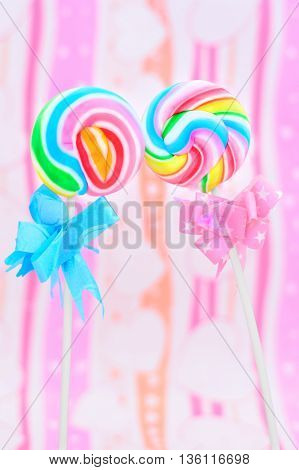 Two rainbow swirl lollipops slightly touching one has a blue bow and the other a pink bow suggesting male and female.