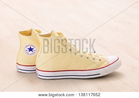BREST BELARUS - JUNE 25 2016: Yellow classic Converse high top sneakers on wooden plank floor