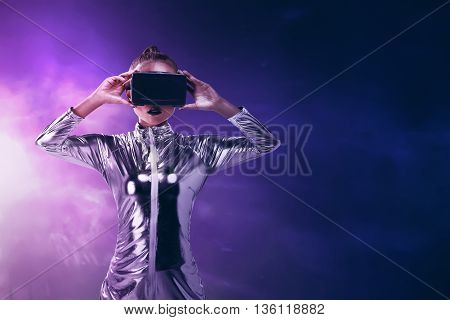 Pretty Asian Woman Wearing Silver Latex Jumpsuit And Vr Headset Inside Virtual World