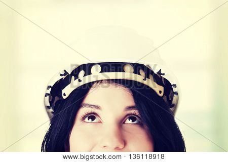 Portrait of female worker in helmet looking up.