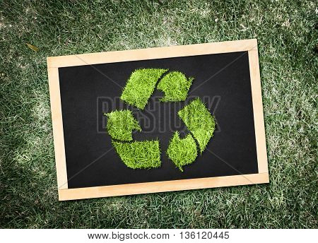 Top View Of Recycle Symbol On Blackboard With Desaturated Green Grass Background, Eco Concept