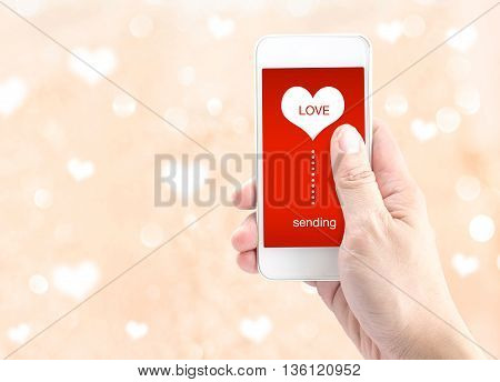 Hand Holding Smartphone With Sending Word And Heart Shape On Screen On Light Bokeh Background, Valen