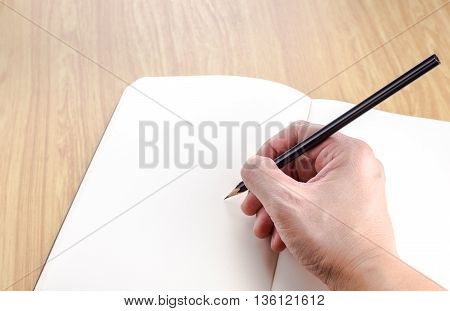 Hand Holding Black Pencil Writting On Blank Open Notebook On Wood Table,business Template