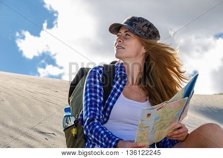 Young beautiful woman backpacker with red hair and freckles traveling in the desert holding the map. Sandy dunes and blue sky on sunny summer day. Travel adventure freedom concept. Toned.