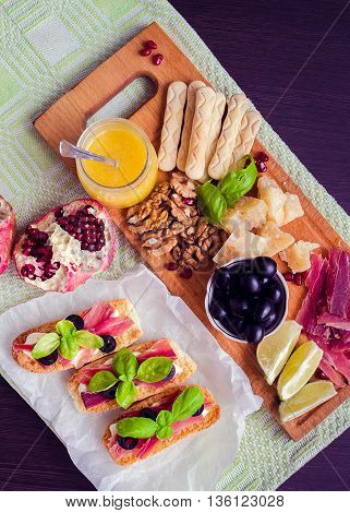 Chopping board with meat and cheese on dark wooden background. Appetizers set. Table full of mediterranean appetizers tapas or antipasto. Italian food. Top view.