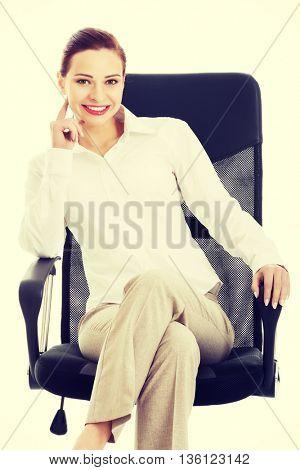 Beautiful business woman, boss sitting on a chair.
