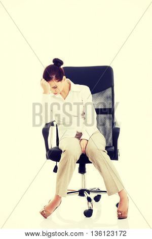 Young beautiful business woman sitting on a chair.