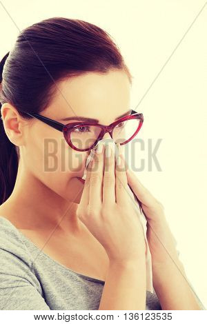Casual beautiful woman in eyeglasses with tissue.