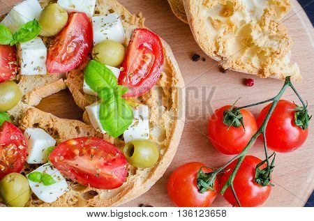 Italian appetizer Friselle. Italian dried bread Friselle on wooden board with tomatoes cherry basil and olives. Italian food. Healthy vegetarian food. A quick and easy snack for party time.