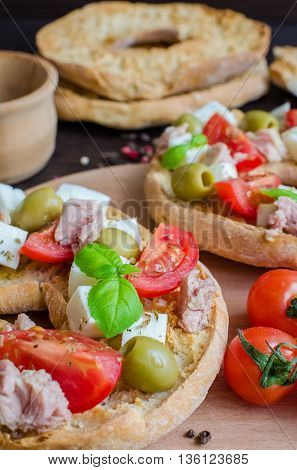 Classical frisella tomato cheese mozzarella tuna and olives. Italian starter friselle. Dried bread called freselle on wooden board with tomatoes cherry. Italian food. Healthy vegetarian food.