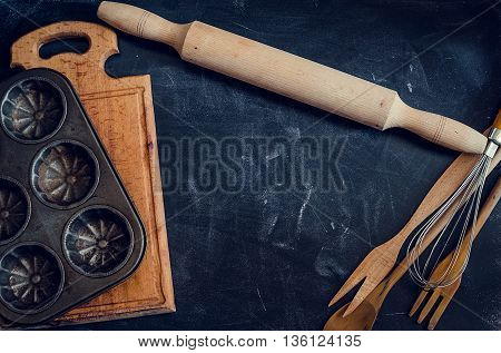 Composition of baking and kitchen accessories on black table. Wooden and metal dishes tableware cookware kitchenware. Different support stuff. Baking preparation concept. Top view. Copy space.
