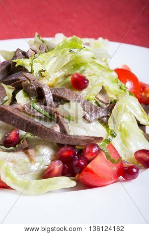Meat salad with mixed lettuce pomegranate and tomatoes