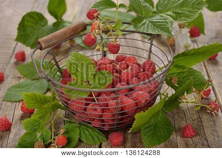 Fresh raspberries in a basket on a wooden background