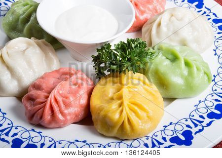 Momos in different colours served with sour cream