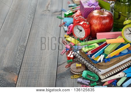 Multicolored children's school supplies on a wooden background
