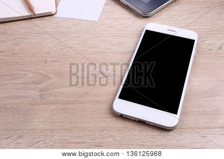 Blank screen smartphone on a wooden background