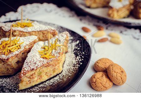 Torta di riso - classical Italian dessert. Rice cake with almonds candied orange peels and amaretto. A slices of rice cake with almond cookies in a plate. Italian food. Selective focus.