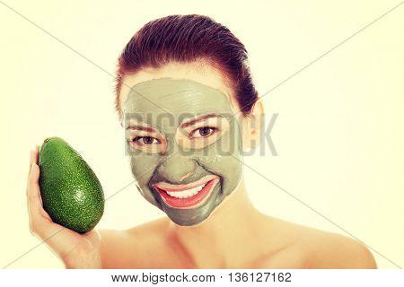 Beautiful woman with facial mask holding avocado.