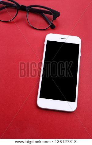 White smartphone on red book and glasses