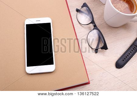 smartphone on book with glasses and coffee on wooden background