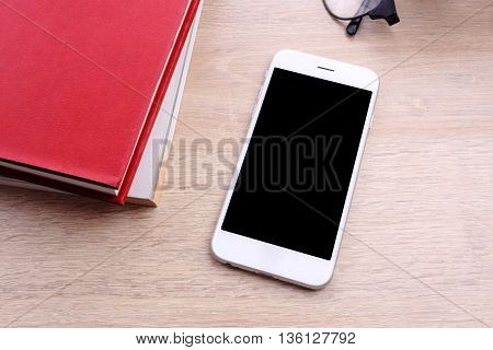 smartphone with red book on wooden background