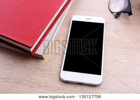 smartphone and book red color on wooden background