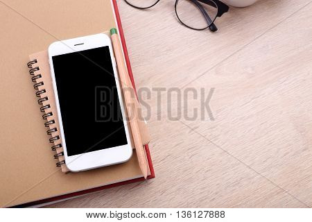 top view blank screen smartphone on book and glasses on wooden background