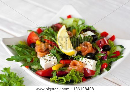 Salmon salad traditional serving with lemon on white wooden background. Top view on white bowl with smoked salmon salad, pepper, brie, olives, lettuce, decorated with slice of lemon.