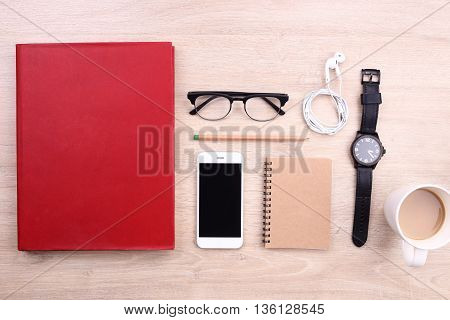 smartphone book and office supplies on wooden background