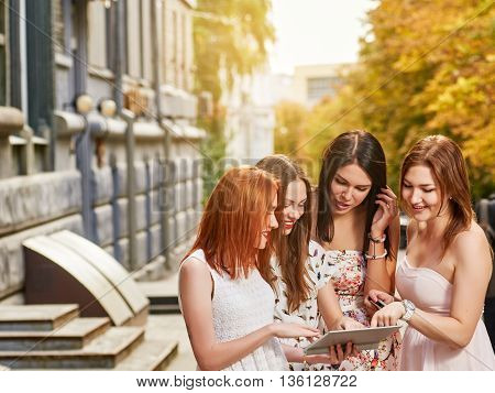 holidays, tourism, technology and internet - four beautiful girls looking at tablet pc computer. autumn outdoor