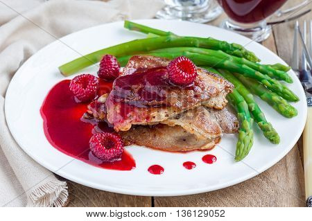 Pork cutlets with raspberry sauce and asparagus on white plate horizontal