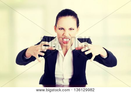 Angry businesswoman at the desk