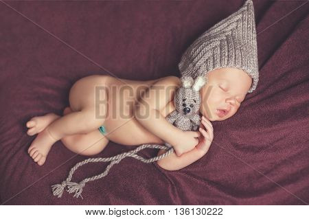 Closeup portrait of newborn baby in gray knitted hat with a grey toy Bunny, a little fluffy hair, sweetly asleep on a dark brown blanket, lying on tummy,put hands behind his head and legs under her