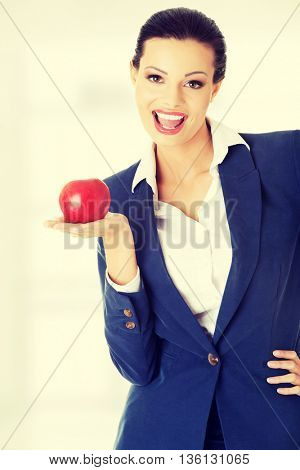 Attractive businesswoman holding red apple