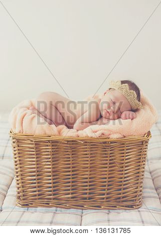 Adorable little guy with little fluffy hairs,in a beige knitted crown,sound asleep on the soft beige blanket in a large wicker basket high,sweet sleeping newborn baby