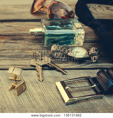 Men accessories: sunglasses, wrist watch, cufflinks, strap, keys, tie, perfume on old wood background. Toned image.
