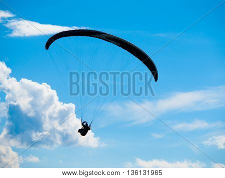 Dark paraglide silhouette on background of blue summer sky and white clouds. Adrenalin sport theme.