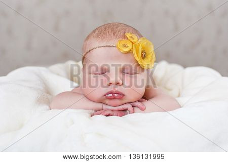 Closeup portrait of newborn child with a yellow flower on the head,little furry hairs, sweetly sleeps on his tummy on the soft white blanket,legs tucked under him and hands resting under his head