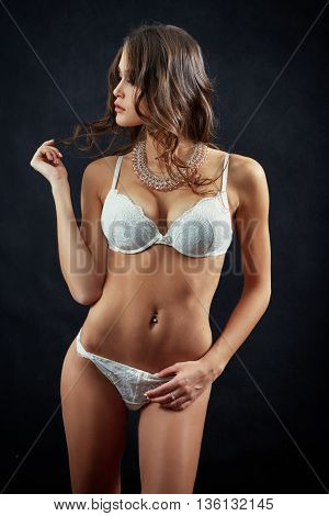 beautiful slim woman in white lingerie on black background