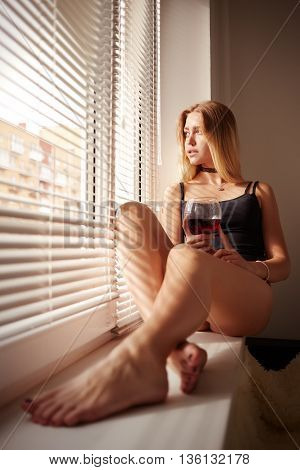 sad woman drinking wine sitting on window