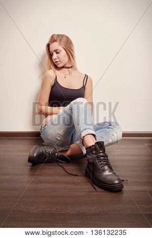 sad pensive blond girl sitting on floor
