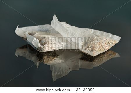 close up of two teabags on black background