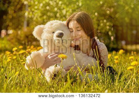 girl with teddy bear lying on dandelion meadow