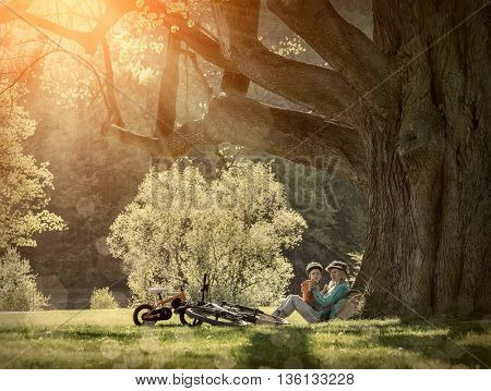 Mother and son with them bicycles in the park under sunlight.