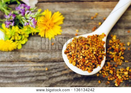 Bee pollen and field flowers on old wooden background. Toned image.