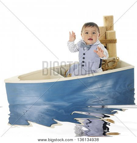 An adorable baby boy sitting alone in a small boat next to mooring posts.  On a white background.