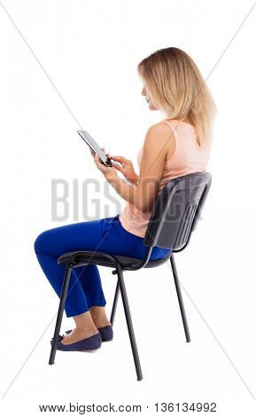 back view woman sitting on chair and looks at the screen of tablet.  Rear view people collection. Blonde in blue pants sitting sideways on office chair and holding horizontally in front of tablet PC